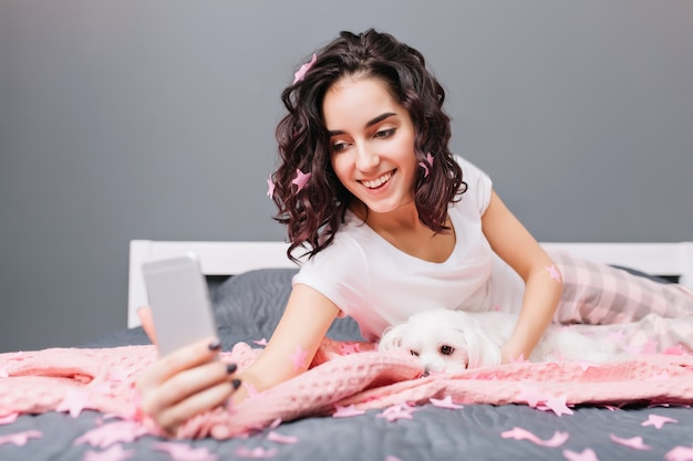 Fazer selfie com cachorrinho doce na cama bordar enfeites rosa de uma jovem morena de pijama. manhã feliz em casa, sorrindo, expressando verdadeiras emoções positivas