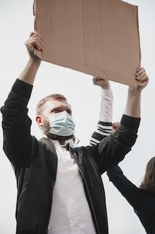 Fé. grupo de ativistas dando slogans em um comício. homem caucasiano e mulher marchando juntos em um protesto na cidade. pareça zangado, esperançoso, confiante. banners em branco para seu projeto ou anúncio.