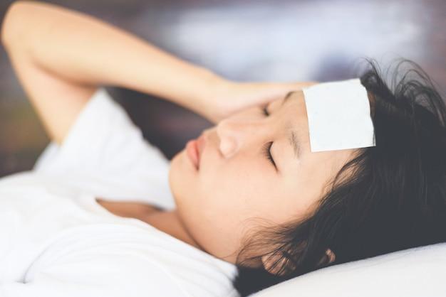 Febre criança com medição de temperatura de criança doente. criança com febre alta e deitado na cama mão segurando na testa.