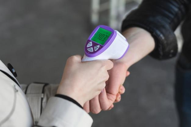 Febre de verificação do operador pelo visitante do termômetro digital no balcão de informações para verificação e proteção contra coronavírus covid-19