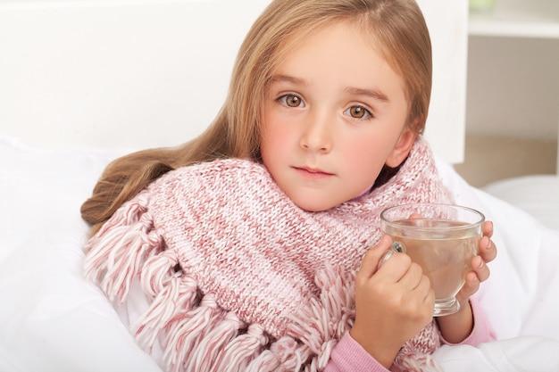 Febre, frio e gripe medicamentos e chá quente em perto, menina doente na cama