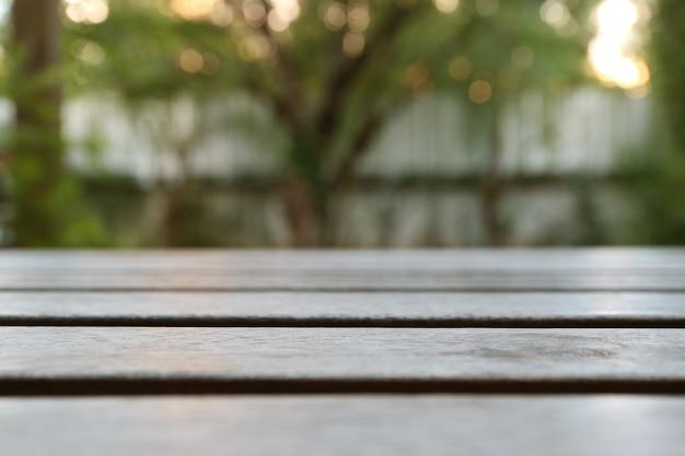 Fechado acima do tampo da mesa de madeira do terraço com grande árvore turva e noite a luz do sol em segundo plano