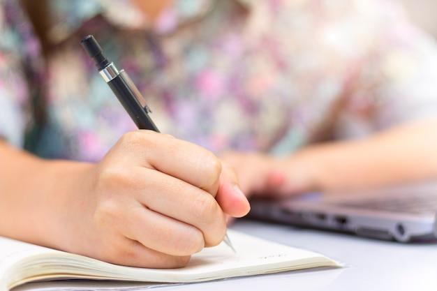 Fechado de mão está escrevendo no notebook