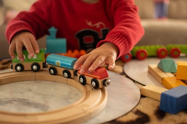 Fechado e macio focado na criança brincando de trem de brinquedo em cima da mesa