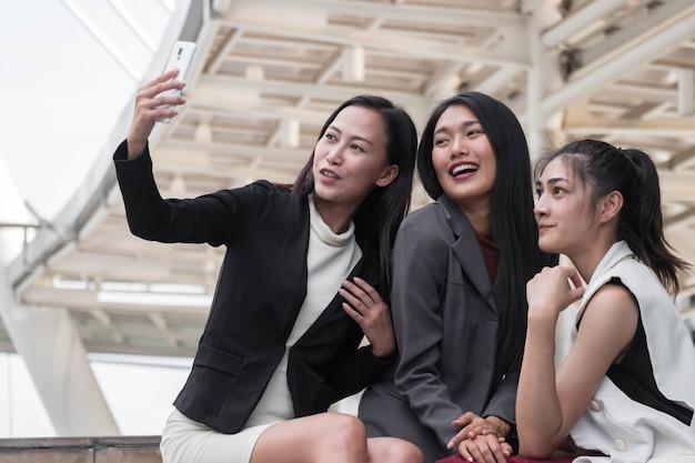 Fechado, jovem, mulher negócio, equipe, ao ar livre, armando, tendo um, selfie