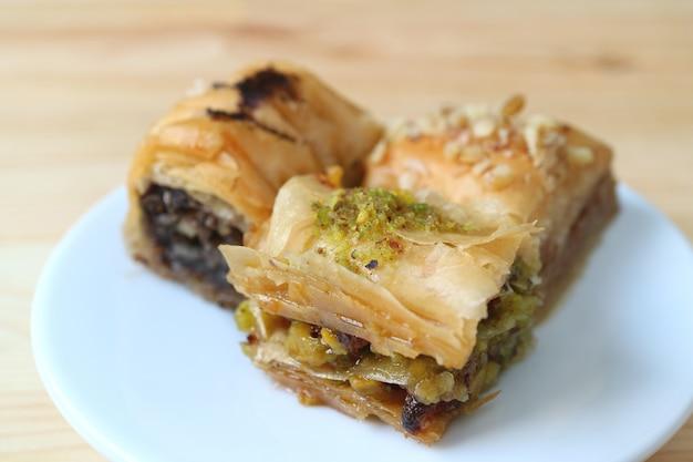 Fechado três tipos de baklava com pistache e nozes, servido na chapa branca, com foco seletivo
