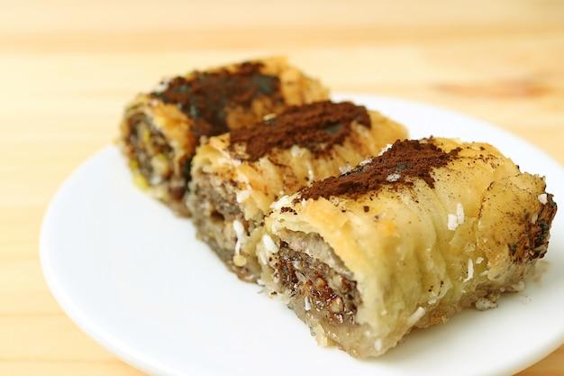 Fechado um lugar de três pedaços de deliciosos doces baklava servidos na mesa de madeira