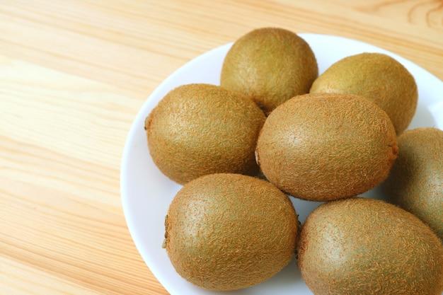 Fechado um prato de frutas frescas de kiwi na mesa de madeira