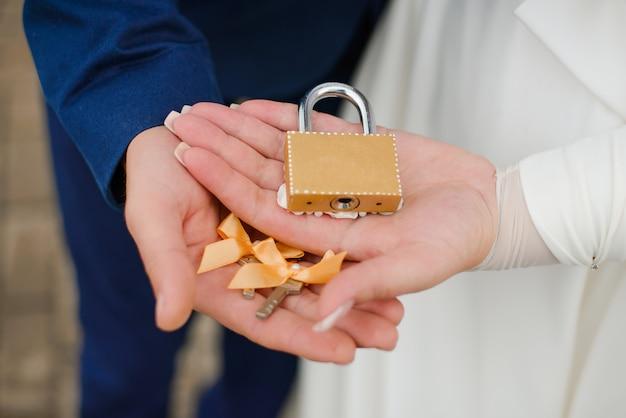 Fechadura de casamento e chaves nas palmas da noiva e do noivo. tradição russa