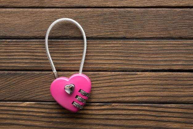 Fechadura de combinação em forma de coração em fundo de madeira