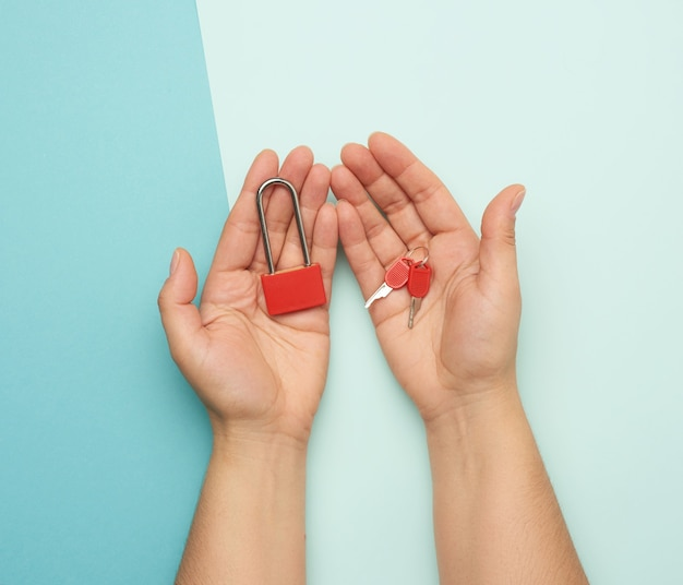 Fechadura de metal com chaves em mãos femininas