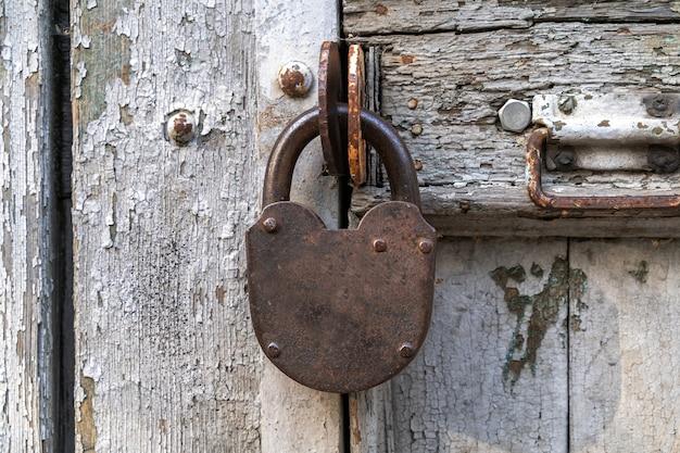 Fechadura de porta de aço velha em uma porta velha e danificada, close-up.