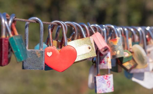 Fechaduras de forma de coração, símbolo da eternidade amor pendurado na cerca da ponte por casal