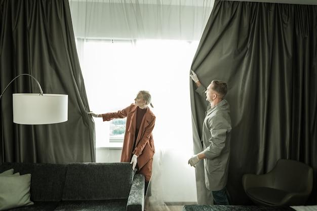 Fechando as cortinas. dois espiões devolvendo apartamentos no estado original com cortinas escuras densas