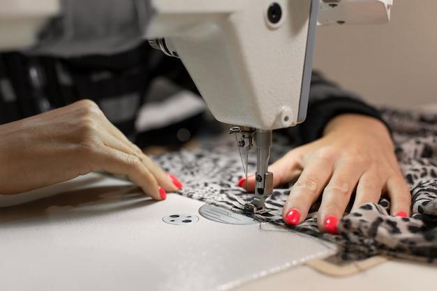 Fechar a costureira mão costura tecido na máquina de costura