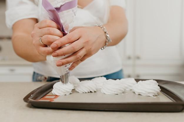 Fechar a foto das mãos de uma mulher colocando o merengue recém-batido em uma bandeja com um saco de confeitar com um asterisco anexado