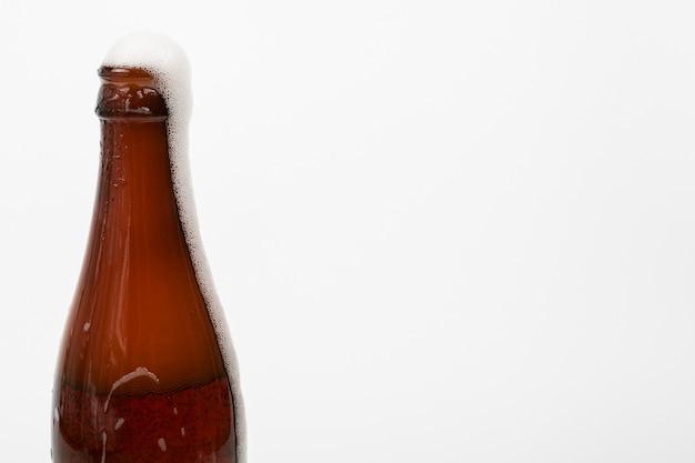 Fechar a garrafa de cerveja e espuma com espaço de cópia