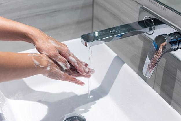 Fechar a mão lavar as mãos na pia, conceito de mãos de limpeza