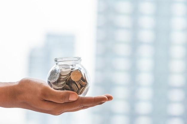 Fechar a mão segurando o dinheiro no copo com espaço de cópia