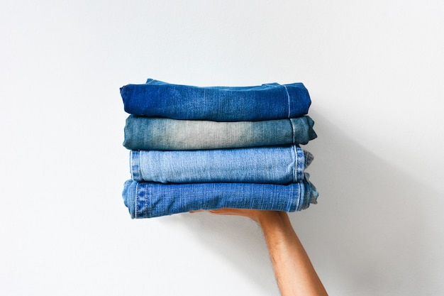 Fechar a pilha de jeans dobrado azul na mão