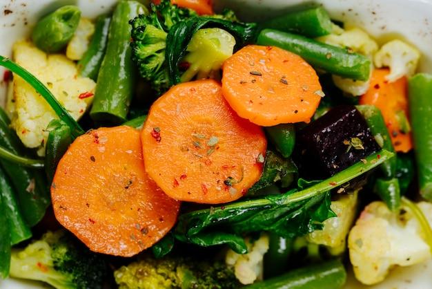 Fechar a vista superior legumes cozidos cenouras aspargos com brócolis em um prato