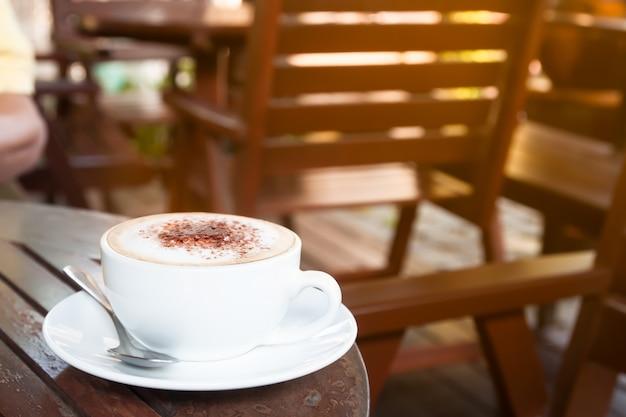 Fechar a xícara de café na mesa de madeira no café, copie o espaço com a luz da manhã