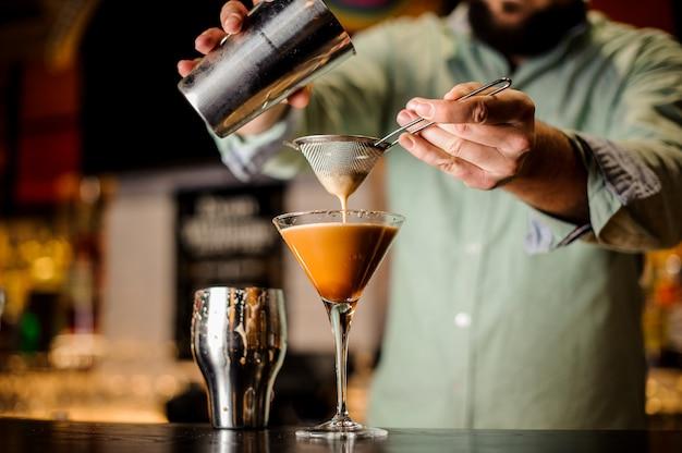 Fechar as mãos barmans com cocktail de café