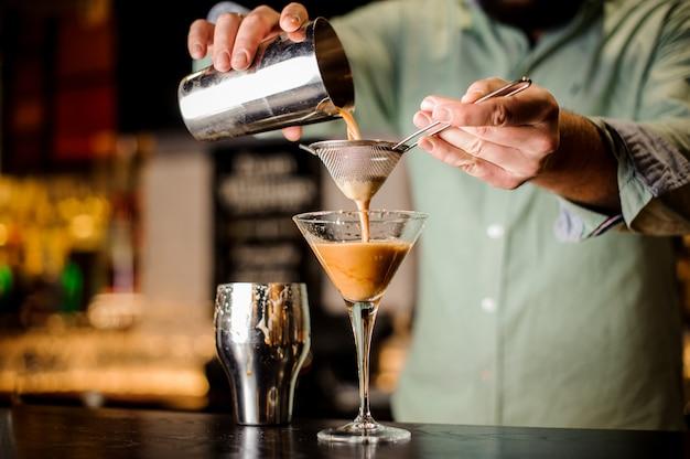 Fechar as mãos barmans com cocktail