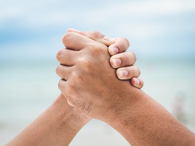 Fechar dois segurando as mãos no fundo do bokeh do mar