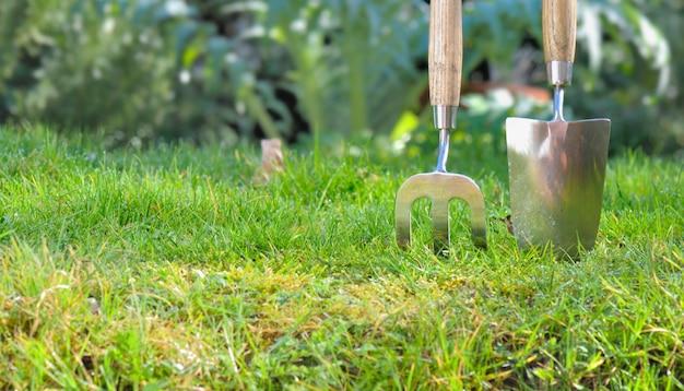 Fechar em metal ferramentas de jardinagem plantio na grama