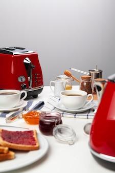 Fechar foto da mesa da cozinha com eletrodomésticos, utensílios de cozinha com torradas e doces