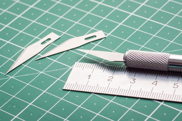 Fechar foto de faca de metal conjunto de lâminas e régua na esteira de corte
