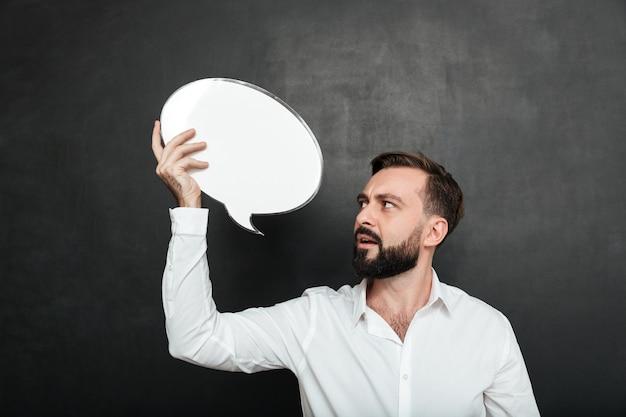Fechar foto de homem atraente, segurando o balão de mensagem em branco e olhando para o anúncio sobre o espaço da cópia de parede cinza escuro