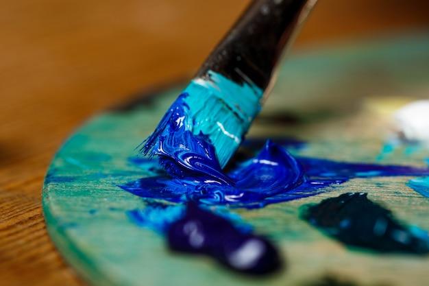 Fechar foto de misturar tintas a óleo na paleta