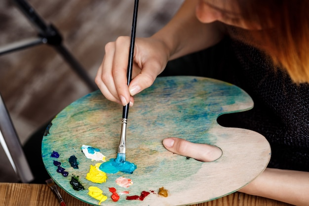 Fechar foto de mulher misturando tintas a óleo na paleta