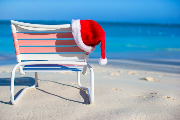 Fechar o chapéu de papai noel na espreguiçadeira na praia tropical