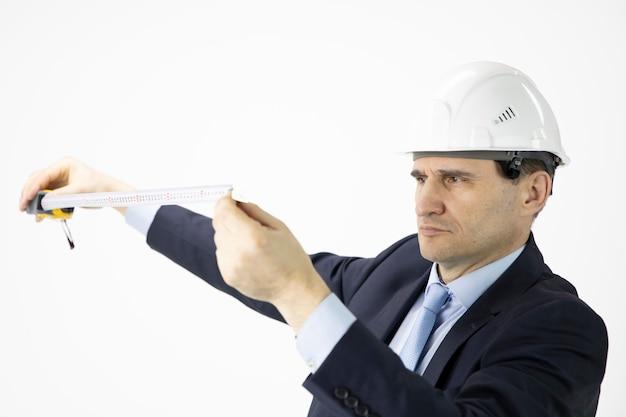 Fechar o engenheiro de construção no capacete de segurança olhando na fita métrica