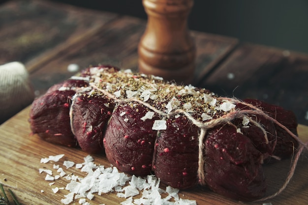 Fechar o foco corda amarrada pedaço de carne salgado apimentado pronto para fumar na mesa de madeira entre ervas