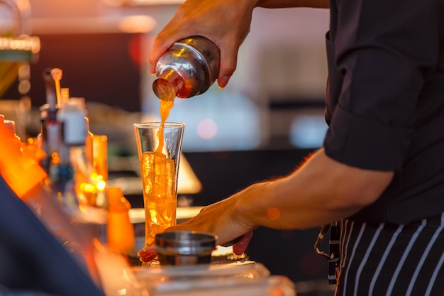 Fechar o processo de preparar um barmen cocktail de maracujá
