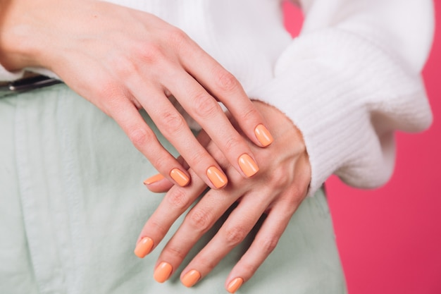 Fechar o quadro das mãos da mulher com manicure laranja no suéter branco e parede rosa