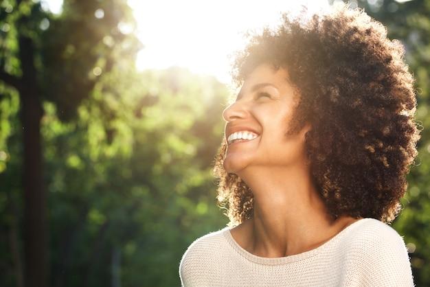 Fechar o retrato da bela mulher confiante rindo na natureza
