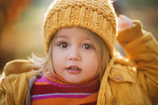Fechar o retrato da menina bonita no chapéu de malha amarelo
