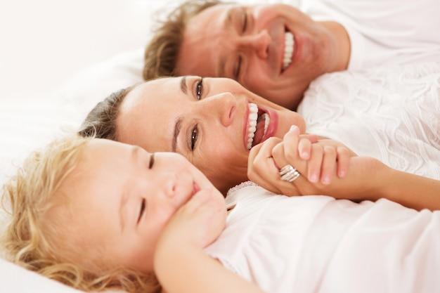 Fechar o retrato da menina bonitinha com os pais deitado na cama em casa e sorrindo