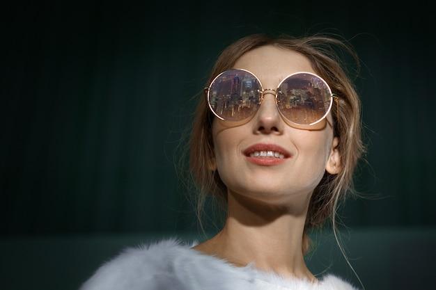 Fechar o retrato da menina loira em óculos de sol com reflexo da cidade