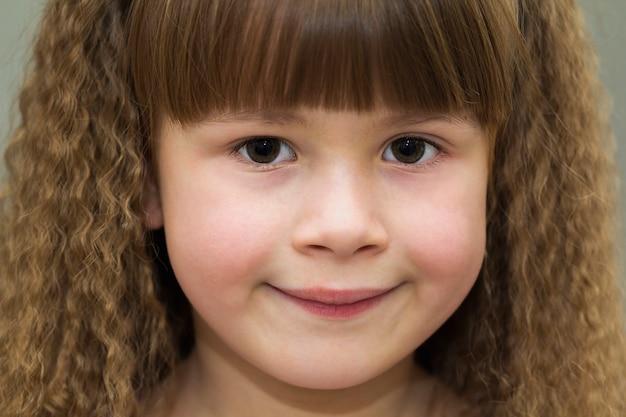 Fechar o retrato da menina sorridente feliz com belos cabelos grossos