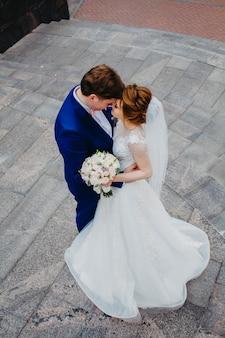 Fechar o retrato de beijar a noiva e o noivo