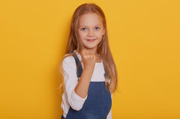 Fechar o retrato de criança do sexo feminino com raiva descontente com longos cabelos loiros