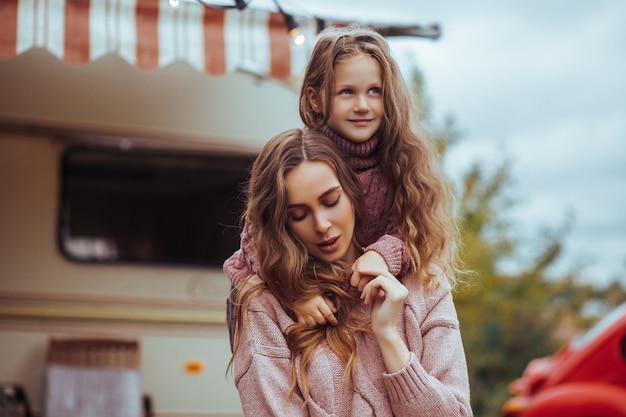 Fechar o retrato de mãe e filha abraçando e relaxando no campo em férias de van campista