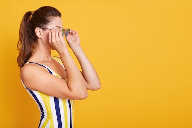Fechar o retrato de mulher jovem vestida de maiô com listras, detém óculos de sol com as duas mãos, posando isolado em amarelo