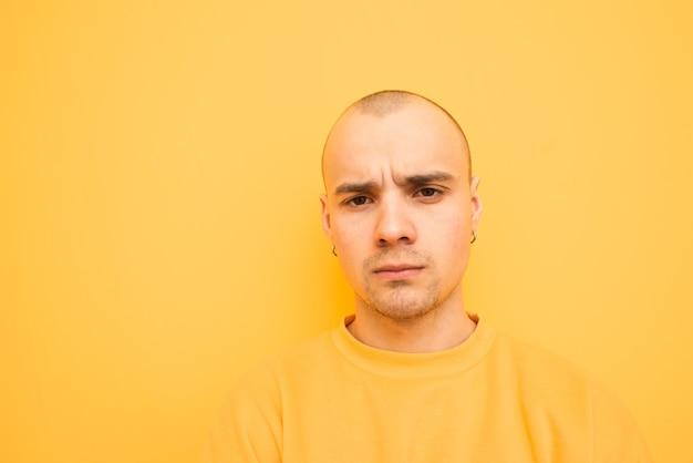 Fechar o retrato de um cara original infeliz com roupas elegantes em um amarelo